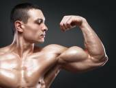 Strong and handsome young bodybuilder demonstrate his muscles an — Stock Photo