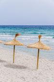 Straw umbrellas on sand beach. — Stock Photo