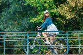 Girl cycles over a bridge. — Stock Photo