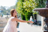 Young woman playing with a fountain — Foto de Stock