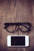 Smartphone and reading glasses — Photo
