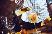 Man pours white homemade sangria — Stockfoto