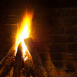 Fire in fireplace, smoked brick wall — Stock Photo #65825715