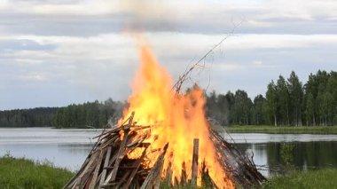 Big midsummer fire at the bank of lake — Stock Video
