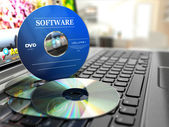 Software CD on laptop keyboard. Compact disks. — Stock Photo
