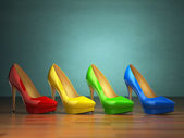 Choice of high heels shoes in different colors on vintage green  — Stockfoto