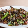 Постер, плакат: Fried edible insects mix on white plate