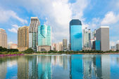 Modern city skyline with reflection in lake under blue sky — Stock Photo
