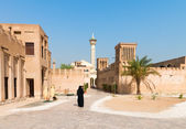 Muslim woman in old arabic district with mosque — 图库照片