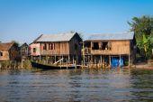Casa tradicional de palafitas e longos barcos na água sob o céu azul — Fotografia Stock