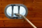 Stainless steel fairlead on a wooden yacht — Stock Photo