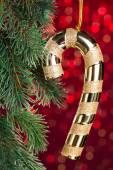 Golden candy cane on shiny background — Stock Photo