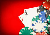 Pair of aces and chips on a red table — Stock Photo