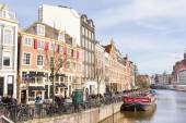 Tourists walking by a canal in Amsterdam — Stock Photo