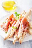 Prosciutto ham and grissini bread sticks. italian antipasto  — Stock Photo