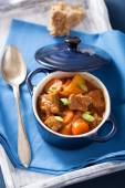 Beef stew with potato and carrot in blue pot — Stock Photo