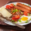 English breakfast with fried egg sausages bacon tomatoes beans — Stock Photo #57068449