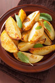 Baked potato wedges in plate over brown rustic table — Stock Photo