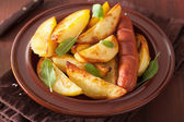 Baked potato wedges and sausage in plate over brown rustic table — Stock Photo