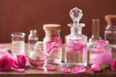 Alchemy and aromatherapy set with rose flowers and flasks — Stock Photo