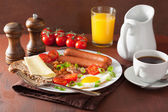 English breakfast with fried egg sausages bacon tomatoes beans — Stock Photo