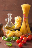 Raw pasta olive oil tomatoes. italian cooking in rustic kitchen — Stock Photo