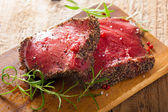 Raw beef steak with spices and rosemary on wooden background — Stock Photo