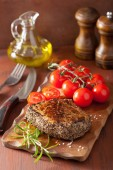 Beef steak with spices and rosemary on wooden background — Stock Photo