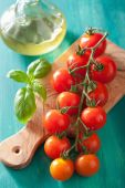 Cherry tomatoes and olive oil over turquoise background — Stock fotografie