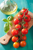 Cherry tomatoes and olive oil over turquoise background — Foto de Stock