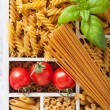 Various raw wholegrain pasta in white wooden box — Stock Photo #74853319