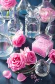 Alchemy and aromatherapy with rose flowers and chemical flasks — Stock Photo