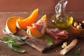 Cantaloupe melon with prosciutto grissini olives. italian appeti — Stock Photo