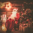 Santa Claus sitting on rocking chair in wooden home interior with illuminated decoration on a wall — Stock Photo #51891285