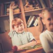 Little redhead schoolboy behind school desk during lesson with his hand up  — ストック写真 #51891683