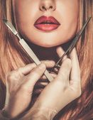 Hands with plastic surgery tools near young woman face  — Stock Photo