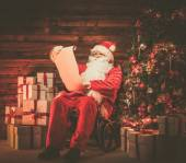 Santa Claus in wooden home interior reading wish list scroll — Stock Photo