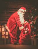 Santa Claus in wooden home interior with sack full of Christmas presents — Стоковое фото