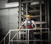 Man in a safety hat on a factory — Stock Photo