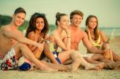 Group of multi ethnic friends with drinks sitting on a beach — Stock Photo