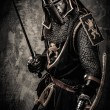 Medieval knight with a sword against stone wall — Stock Photo #52445347