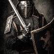 Medieval knight with a sword against stone wall — Stock Photo #52445351