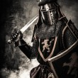 Medieval knight with a sword against stone wall — Stock Photo #52445373