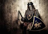 Medieval knight on golden wall background — Stock Photo