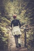 Hiker with hiking poles looking walking over wooden bridge in a forest  — Stock Photo