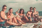 Group of multi ethnic friends with drinks relaxing on a beach — ストック写真