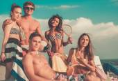 Group of multi ethnic friends with drinks relaxing on a beach — Foto de Stock