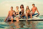 Group of multi ethnic friends sitting on a jet ski — Foto de Stock