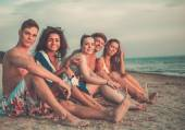 Group of multi ethnic friends with drinks relaxing on a beach — Stockfoto