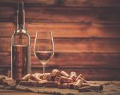 Bottle and glass of white wine on a wooden table among corks  — Stockfoto